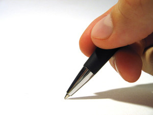 [photo of a hand holding a pen and writting]