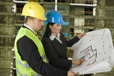 [picture of two people studying a construction site map]